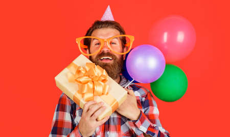 Man in holiday cap with balloons and present box. Happy birthday, holidays. Party time. Festive event. Standard-Bild