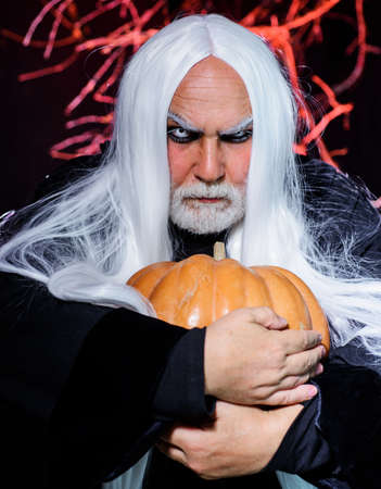 Devil man with pumpkin in hand. Bearded man in witch costume ready to Halloween party. Standard-Bild