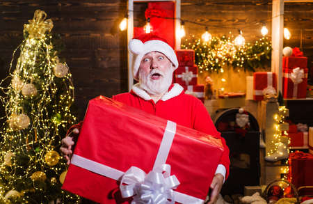 Surprised Santa Claus with gift box. Santa man with big present. New year advertising. Merry christmas. Standard-Bild
