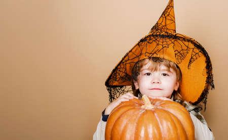 Happy Halloween. Cute boy in witch hat with big pumpkin. Jack-o-lantern. Trick or treat. Copy space. 31 october. Standard-Bild