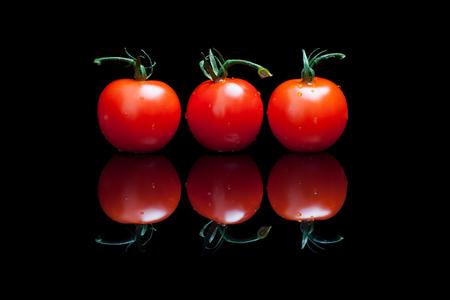 Three tomatoes on a black shiny background Stock Photo