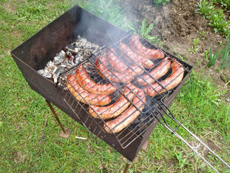 Grilling sausages on barbecue grill photo