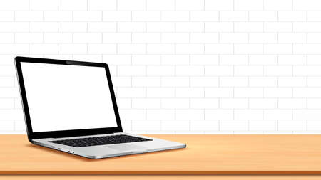 Laptop on table against white wall