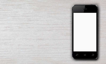 Black smartphone with white blank screen lying on a wooden table