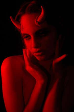 魅惑的な見ている角を持つ女性の悪魔の写真
