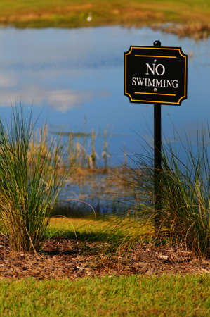 No swimming sign posted in front of a small body of water Stock Photo - 3972539