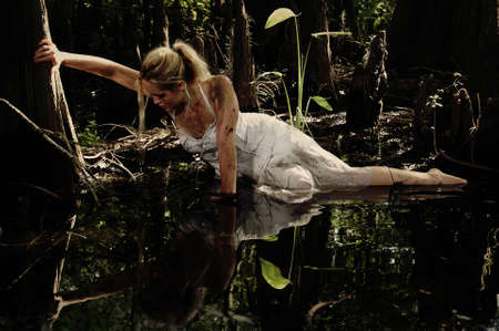 Girl grasping a tree trying to get out of a muddy bog