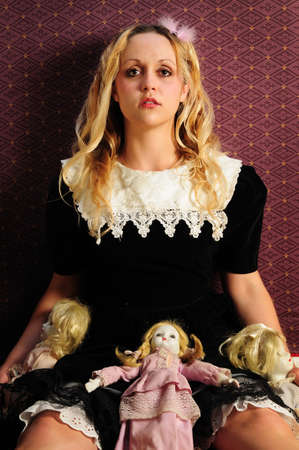motionless: Doll-like girl leaning against wall and surrounded by porcelain dolls