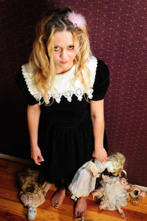 Pop-achtige meisje in frilly jurk staande te houden porseleinen pop kant op. Andere gebroken poppen tot op de vloer. Stockfoto
