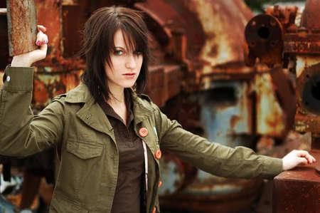 Mooi jong meisje draagt militair geïnspireerde kleding onder roestige machines Stockfoto