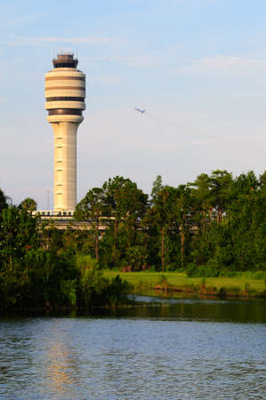 air traffic: Air traffic control tower with plane taking off in background