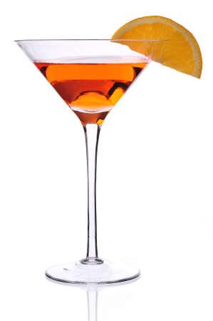 Isolated shot of martini glass with orange liquid and orange slice