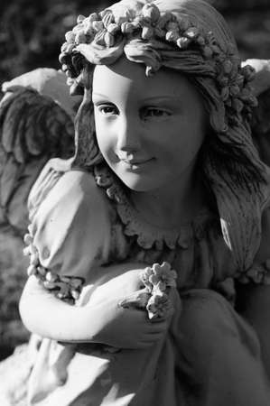 A statue of a young female angel holding flowers and smiling
