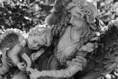 angel cemetery: An older angel showing a book to a young child-like angel Stock Photo
