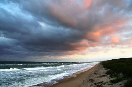 Storm wolken waait over oever van ongerepte Florida strand bij zonsondergang.