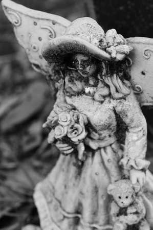 Griezelig zwart-wit beeld van een jonge engel bedrijf bloemen en een teddybeer Stockfoto