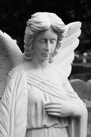 head bowed: Black and white photo of an angel statue with its eyes closed and head bowed