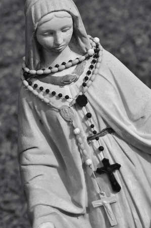 A vrgin Mary statue with a couple rosaries around its neck photo