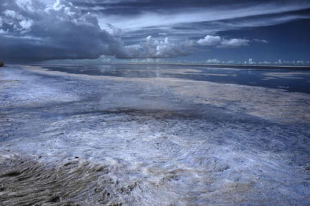 Infrarood opname van een lagune met donkere dreigende wolken op de horizon Stockfoto