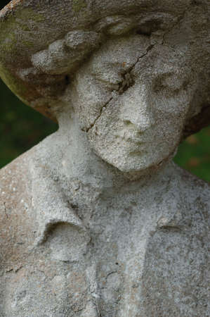 An old weathered statue of a sad looking man with a cracked face