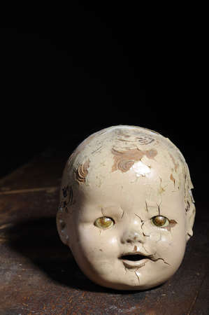 horrors: Creepy old doll head sitting on weathered wood