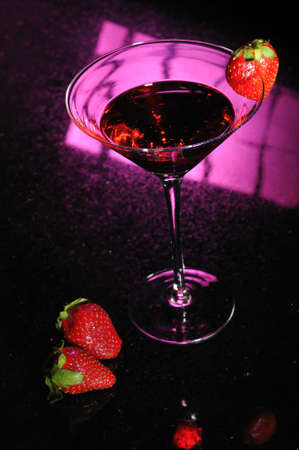 A martini glass with red liquid and a strawberry and two strawberries off to the side photo