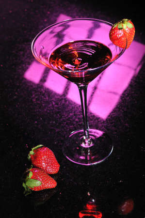 A martini glass with red liquid splashing up in center and a strawberry placed on side with two strawberries next to glass photo