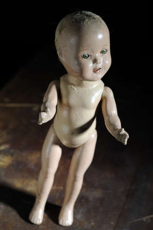 Creepy antique doll standing on distressed wooden background