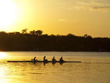 Een team van jonge betekenen in een roeiboot silouhetted tegen de ondergaande zon Stockfoto