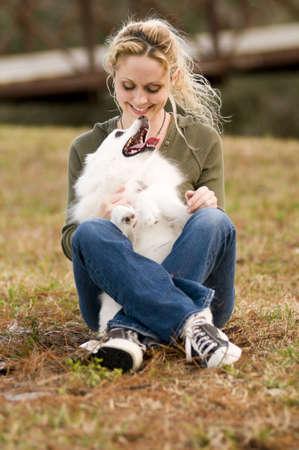 eskimo woman: a young woman holding an American Eskimo dog