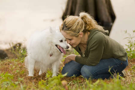 eskimo woman: a young woman with her head against an American Eskimo dog Stock Photo