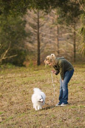 a girl walking her dog through a park