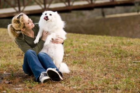 a young woman holding an American Eskimo dog photo