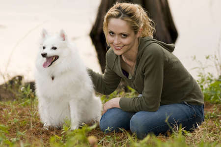 eskimo woman: A young woman siting in grass petting her American Eskimo dog Stock Photo