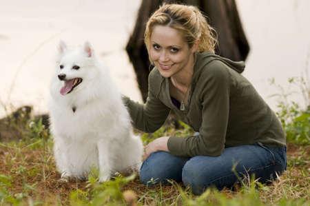 Een jonge vrouw aanbrengen in gras haar Amerikaanse Eskimo hond aaien  Stockfoto