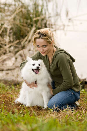 Young woman holding an American Eskimo dog Stock Photo - 6342153
