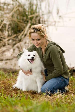eskimo woman: Young woman holding an American Eskimo dog
