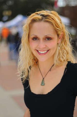Portret van lachende jonge vrouw met een out of focus street fair in achtergrond