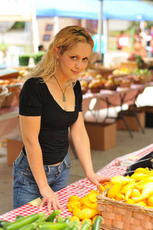 Young woman at a farmers market vegtable stand photo