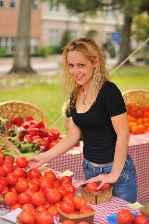 a young woman selecting tomatoes from a farmer's market photo
