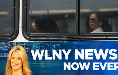 New York City, NY USA. July 15 2014. A Hispanic lady on a city bus with headphones listening to mobile media and local news as advertised on bus. Редакционное