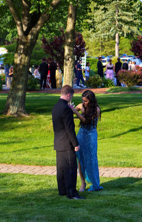 Plainville, CT USA. June 2013. Young woman is cautiously pinning her date`s boutonniere before the prom.