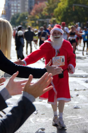 New York City, NY USA. Nov 2008. A running New York City Marathon Santa Claus greeting and shaking some hands from the crowd. 新聞圖片