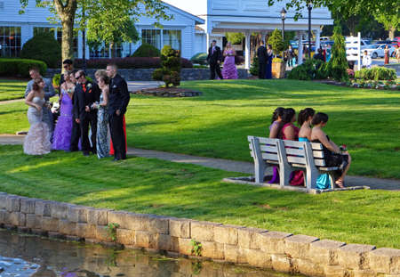 Plainville, CT USA. June 2013. Seniors posing for photographers and classmates while focused group on the left looking at the fish in pond. Redactioneel
