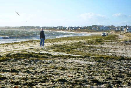 Cape Cod, MA USA. Nov 2018. An elderly man walking towards a truck stuck in the beach sand during a northern Arctic Blast hitting New England.