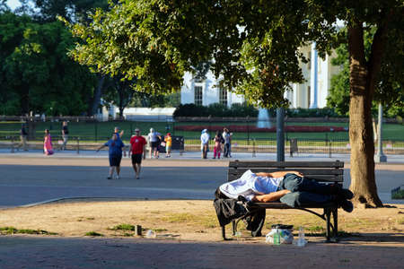 Washington, DC USA. Jul 2016. Homeless man sleeping on a park bench across the White House, A sad contrast between wealth and power, and poverty. Éditoriale