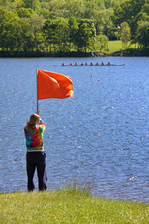 New Preston, CT USA. May 2010. A young women raising the finishing flag at a crew rowing race. Redactioneel