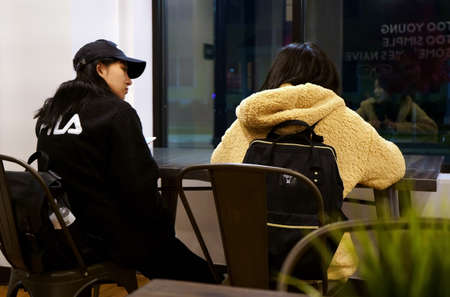 Storrs, CT USA. Nov 2018. Asian foreign exchange students taking a break at a campus eatery.