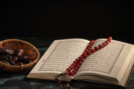 Islamic concept for eid and ramadan: The holy qoran with tasbih (rosary beads) and dates