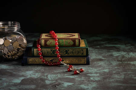 Zakat concept: Jars fulls with coins and money with the holy qoran. copy space for text Reklamní fotografie